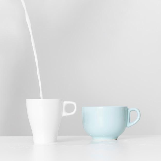 Melk gieten in keramische mok op een tafel Gratis Foto