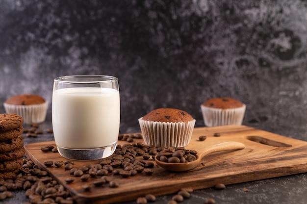 Melk in een glas, compleet met koffiebonen, cupcakes, bananen en koekjes op een houten plaat. Gratis Foto