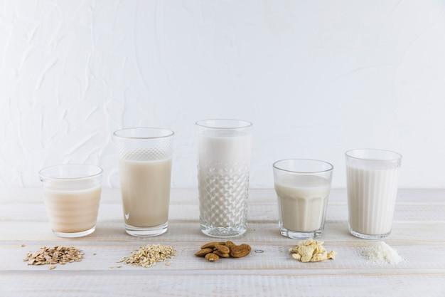 Melk in verschillende soorten glazen en granen Gratis Foto