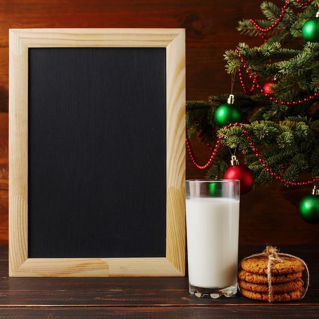 Melk, koekjes en een verlanglijstje onder de kerstboom. de komst van de kerstman. Premium Foto