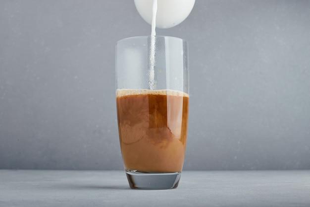 Melk toevoegen aan het glas cappuccino. Gratis Foto