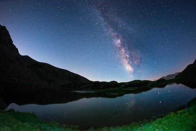 Melkweg boog en sterrenhemel weerspiegeld op meer op grote hoogte op de alpen Premium Foto