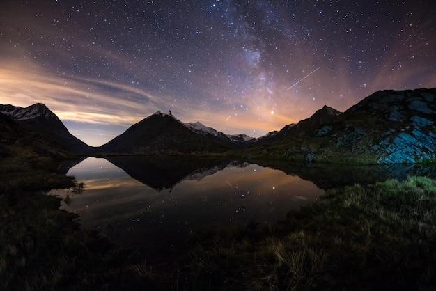 Melkweg sterrenhemel weerspiegeld meer op grote hoogte op de alpen Premium Foto