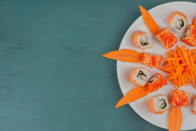 Meng sushi met plakjes wortel op een witte plaat Gratis Foto