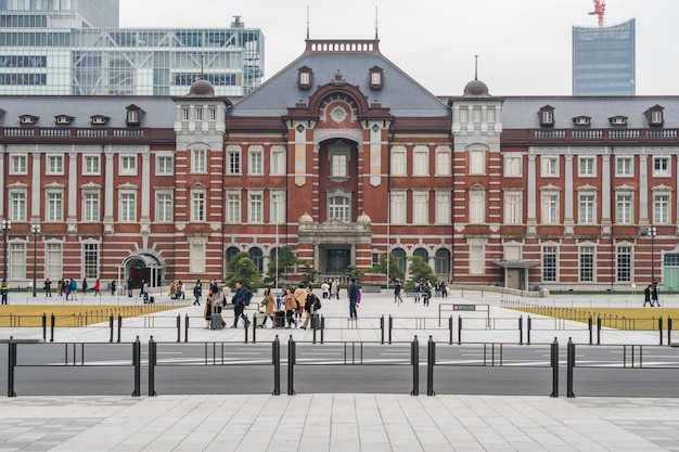Menigte onbekende mensen die een bezoek brengen aan en genieten van tokyo station en marunouchi met autoverkeer tokyo Premium Foto