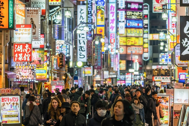 Menigte onbekende mensen die rond de straat van de avondmarkt lopen in kabukicho van shinjuku station Premium Foto
