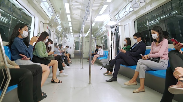 Menigte van mensen die een gezichtsmasker dragen op een drukke openbare metro Premium Foto