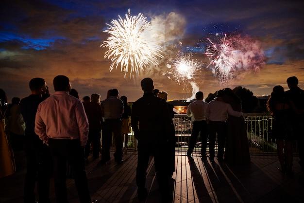 Menigte van mensen kijken naar vuurwerk in de avondlucht Premium Foto
