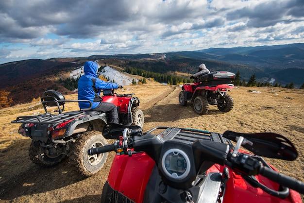 Mening van een vierlingfiets met mensen die een atv vooraan op de bovenkant van bergsleep drijven Premium Foto
