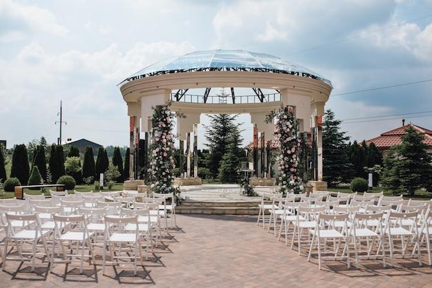 Mening van gastzetels en ceremoniële huwelijksboog op zonnig zeg, chiavari-stoelen, verfraaid gebied Gratis Foto