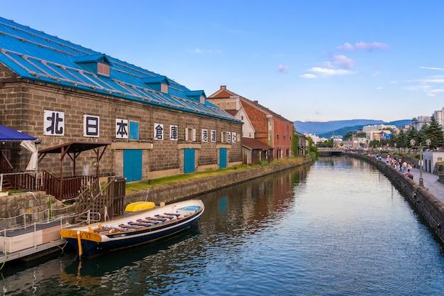 Mening van otaru-kanaal met toeristenboot en blauwe hemel in de zomer in otaru, hokkaido, japan. Premium Foto