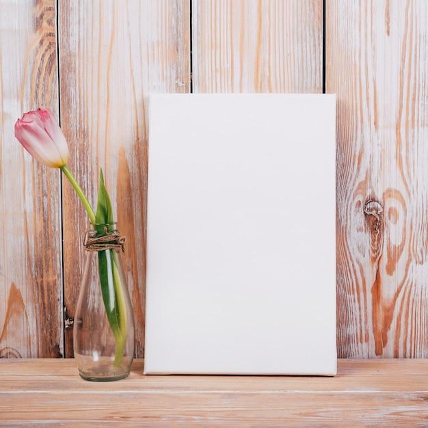 Mening van tulpenbloem in vaas met zwart aanplakbiljet op houten achtergrond Gratis Foto