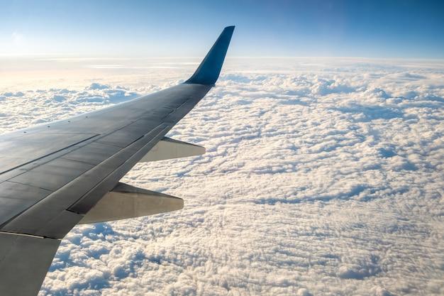 Mening van vliegtuig op de vliegtuigen witte vleugel die over bewolkt landschap in zonnige ochtend vliegen. vliegreizen en transport concept. Premium Foto
