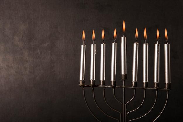 Menorah met kaarsen dichtbij grijze muur Gratis Foto