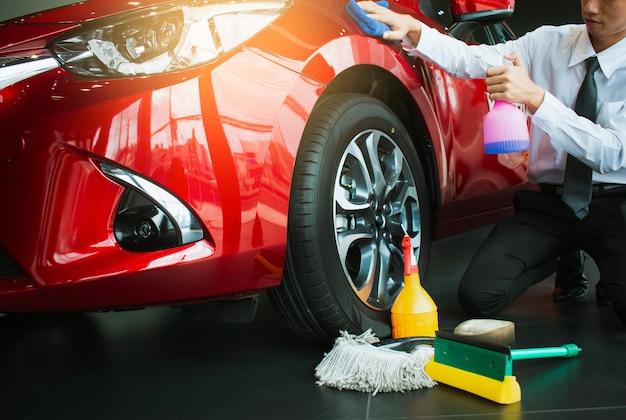 Mens aziatische inspectie en schoonmakende materiaalautowasserette met rode auto Premium Foto