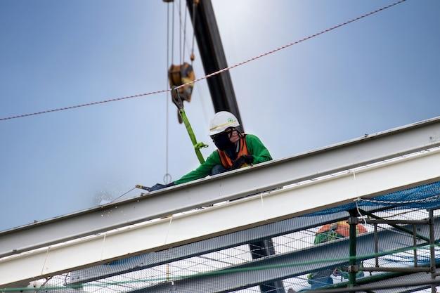Mens die aan bouwwerf met steiger werkt en met zonachtergrond bouwt, steiger voor bouwfabriek Premium Foto