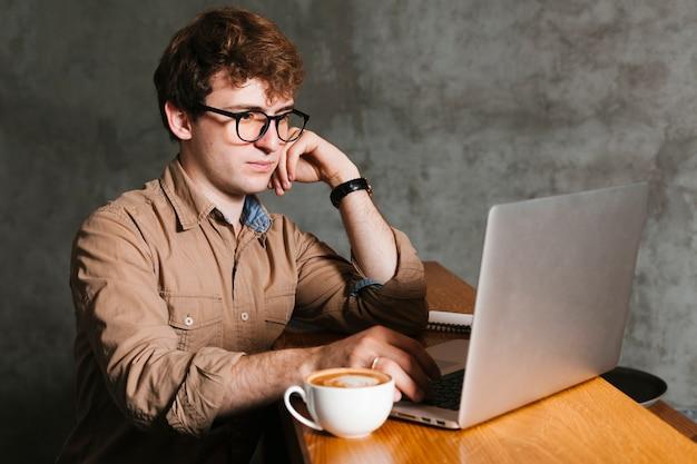 Mens die aan laptop in het bureau werkt Gratis Foto