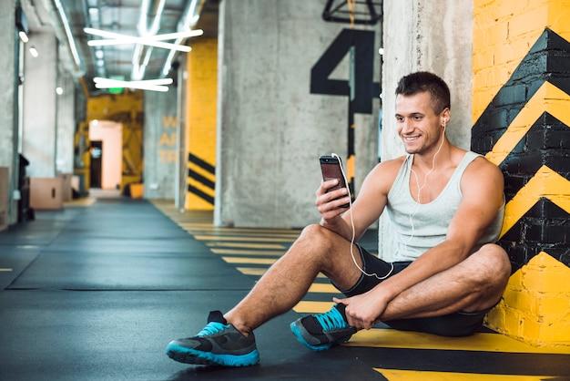Mens die aan muziek op cellphone in gymnastiek luistert Gratis Foto