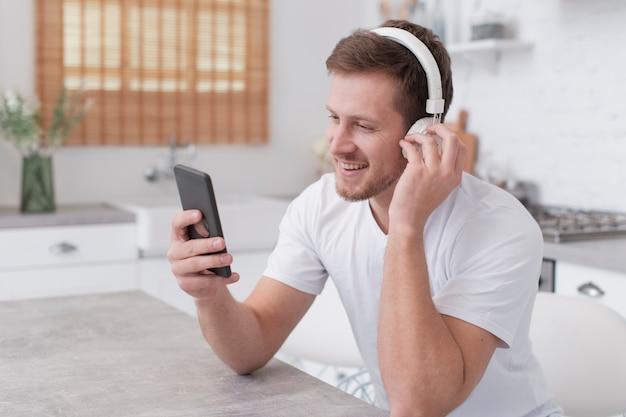 Mens die aan muziek op witte hoofdtelefoons luistert Gratis Foto