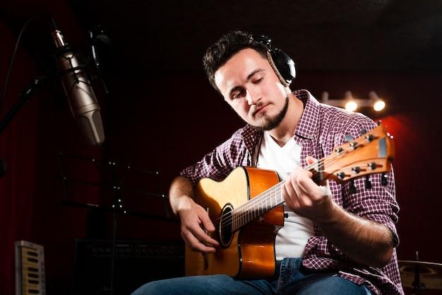 Mens die akoestische gitaar opneemt en hoofdtelefoons draagt Gratis Foto