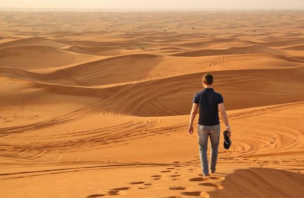 Mens die alleen in de zonnige woestijn naast doubai loopt Premium Foto