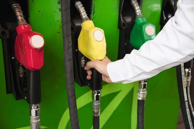 Mens die benzinebrandstof in zijn auto in een pompbenzinestation zet Gratis Foto