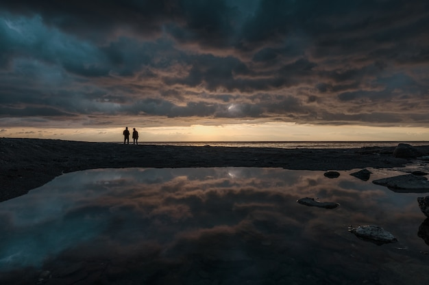 Mens die bij zonsopgang op de lijn van horizon vist Gratis Foto