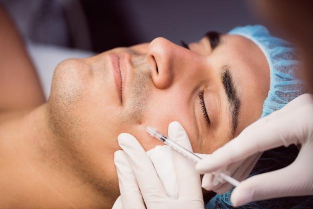 Mens die botox injectie op zijn gezicht ontvangt Gratis Foto