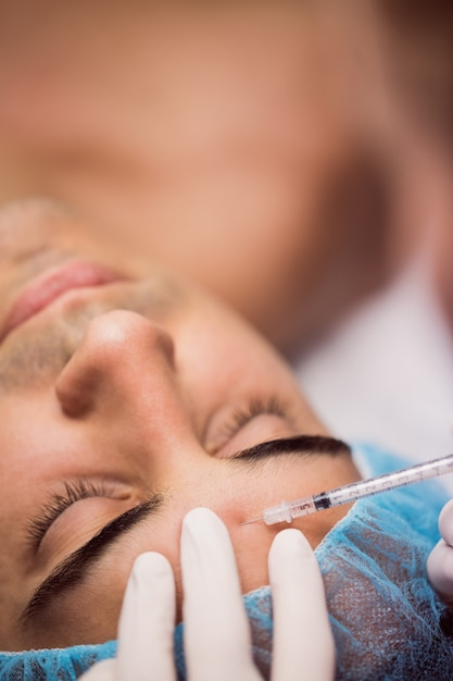 Mens die botox injectie op zijn voorhoofd ontvangt Gratis Foto