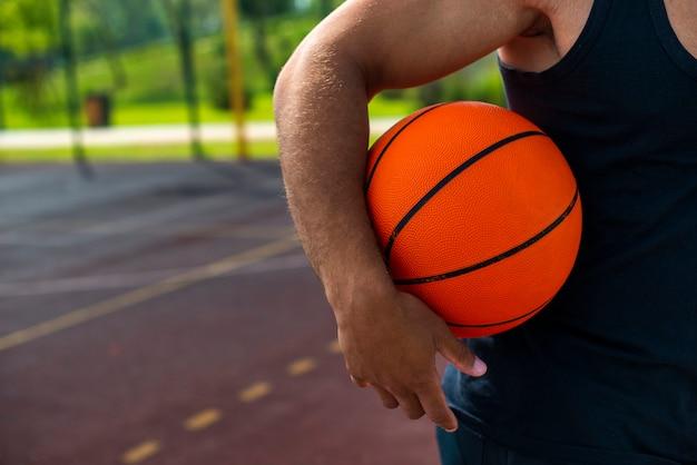 Mens die de bal op het close-up van het basketbalhof houdt Gratis Foto