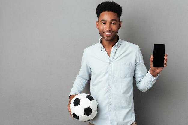Mens die de lege mobiele telefoon van het scherm tonen en voetbal houden Gratis Foto