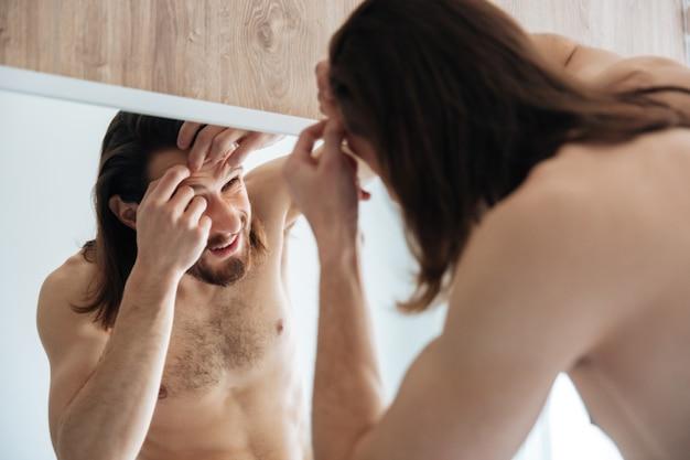 Mens die de spiegel bekijkt en puistje in badkamers drukt Gratis Foto