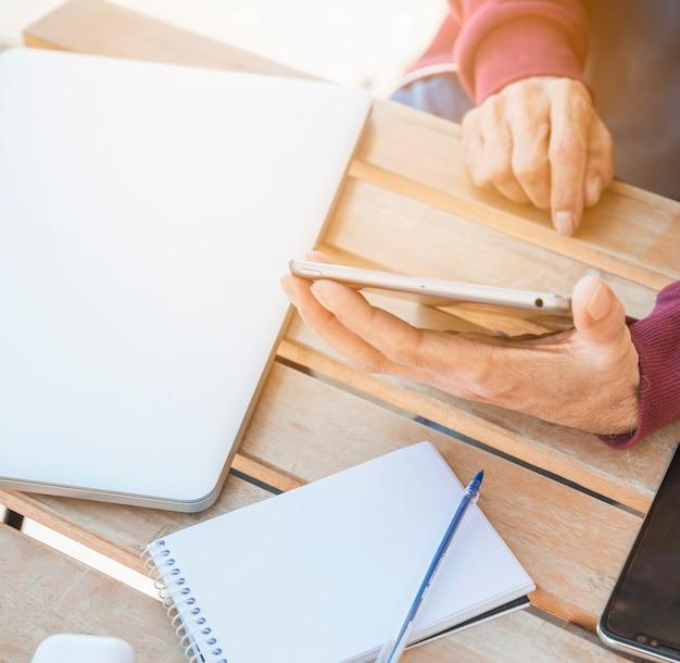 Houten Bureau Gebruikt.Mens Die Digitale Tablet Met Laptop Gebruikt Spiraal Kladblok En