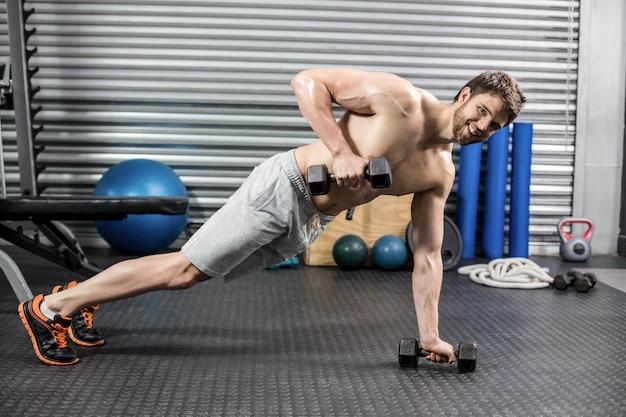 Mens die duw omhoog met dumbells doen bij crossfitgymnastiek Premium Foto