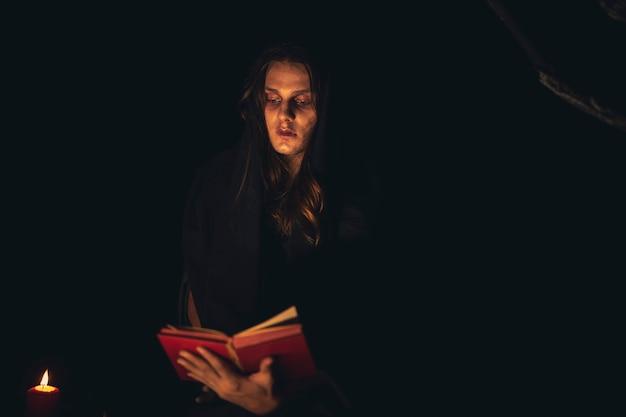 Mens die een betoveringsboek in het donker leest Gratis Foto