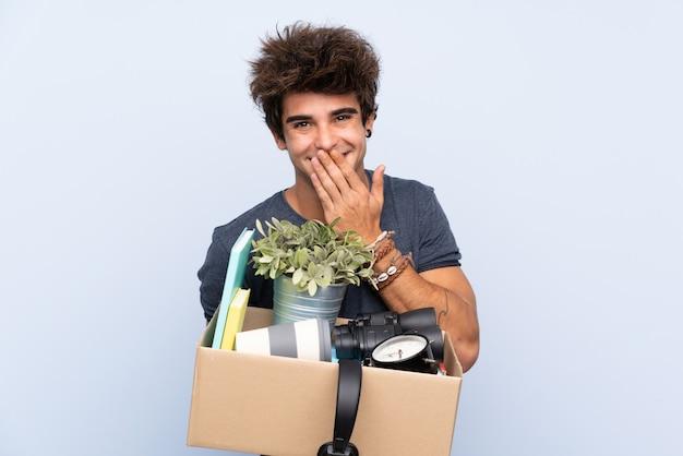 Mens die een beweging maakt terwijl het oppakken van een doos vol dingen met verrassende gelaatsuitdrukking Premium Foto