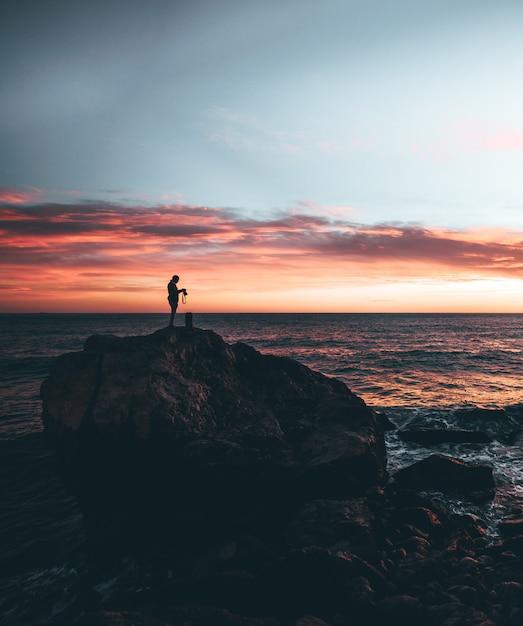 Mens die een camera in de bovenkant van een rots met een zonsondergang houdt Premium Foto