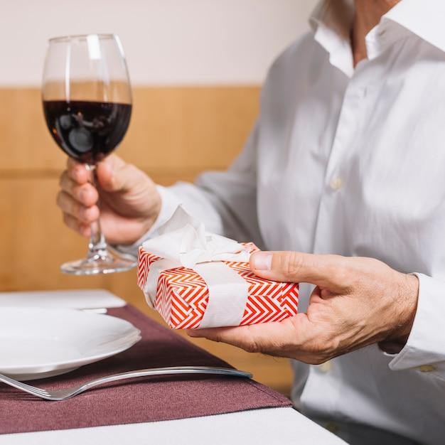 Mens die een glas wijn en gift houdt Gratis Foto