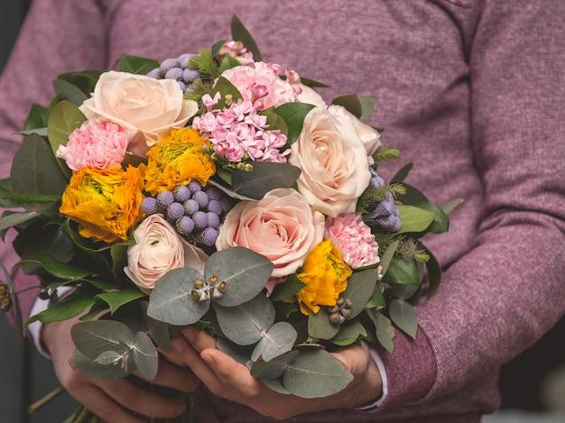 Mens die een romantisch boeket van gemengde selectiebloemen houdt en klaar aan te bieden Gratis Foto