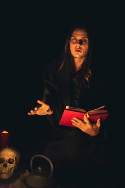 Mens die een rood werktijdboek in het donker leest en camera bekijkt Gratis Foto