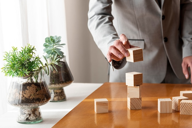 Mens die een stapel van houten dozen bouwt Gratis Foto