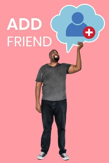 Mens die een symbool van het vriendenverzoek voor sociaal netwerk houdt Gratis Foto