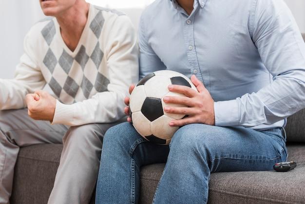 Mens die een voetbal met handen houdt Gratis Foto