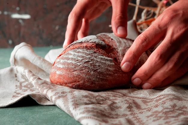 Mens die eigengemaakt tarwebrood met bloem op het op een witte handdoek met twee handen zet. Gratis Foto