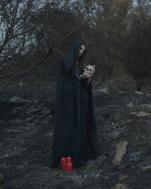 Mens die en een schedel voor halloweenpartij bevinden zich houden Gratis Foto