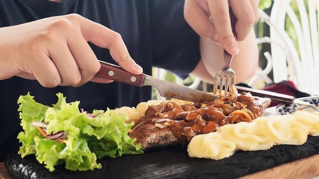 Mens die het recept van het varkensvleeslapje vlees eet Gratis Foto