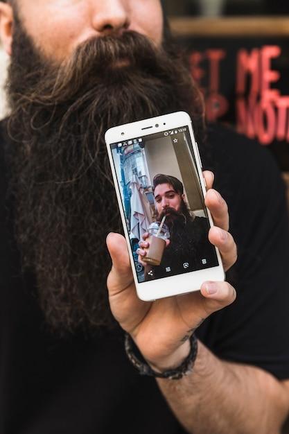 Mens die hoge foto op het slimme telefoonscherm toont Gratis Foto