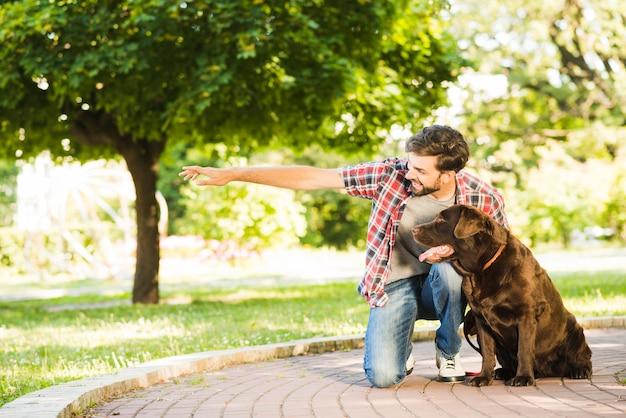 Mens die iets toont aan zijn hond in park Gratis Foto