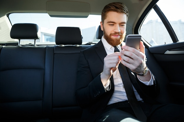 Mens die in kostuum mobiele telefoon in zijn hand bekijkt Gratis Foto