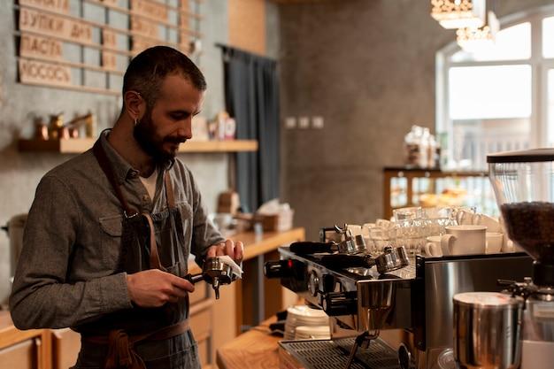 Mens die in schort koffie voorbereiden bij machine Gratis Foto
